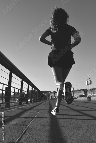Fotografie, Obraz Running girl in Bordeaux on the quais with shadow in the early morning