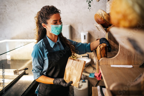 Foto Beautiful young female worker with protective mask on face working in bakery
