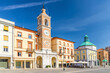 Piazza Tre Martiri Three Martyrs square with traditional buildings with clock and bell tower in old historical touristic city centre Rimini with blue sky background, Emilia-Romagna, Italy