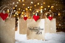 Christmas Shopping Bags On Snow With German Calligraphy Frohe Weihnachten Und Ein Glueckliches 2021 Mean Merry Christmas And Happy 2021. Bright Glowing Lights In Background And Snowflakes