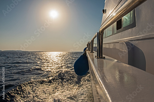 Fototapeta View from a yacht travelling at sunrise