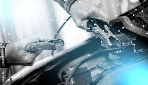 Fototapeta Hands of car mechanic using car battery jumper cable; light effect