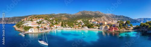 Panoramablick auf das idyllische Dorf Asos mit türkisem Meer, Segelbooten und bunten Häusern direkt am Meer, Kefalonia, Griechenland