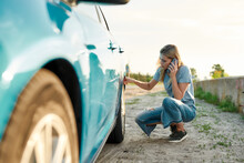 Attractive Young Woman Looking Sad, Calling Car Service, Assistance Or Tow Truck While Having Troubles With Her Auto, Checking Wheel After Car Breakdown On Local Road Side