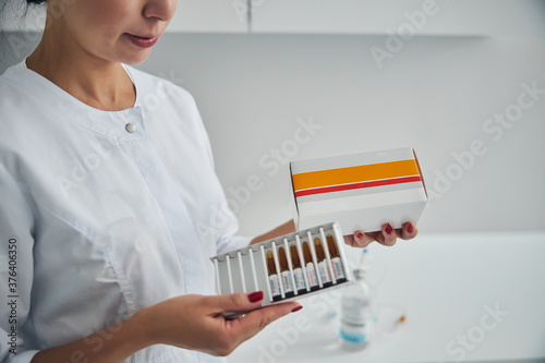 Female cosmetologist preparing for administering an injection Wallpaper Mural
