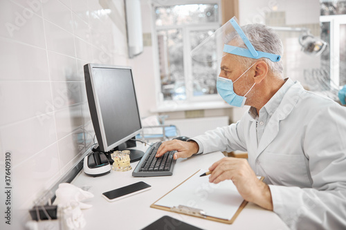 Obraz Busy healthcare professional looking at a computer screen - fototapety do salonu
