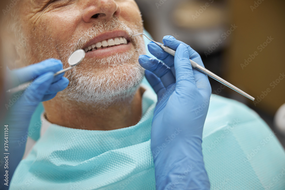 Fototapeta Calm elderly man smiling during dental examination
