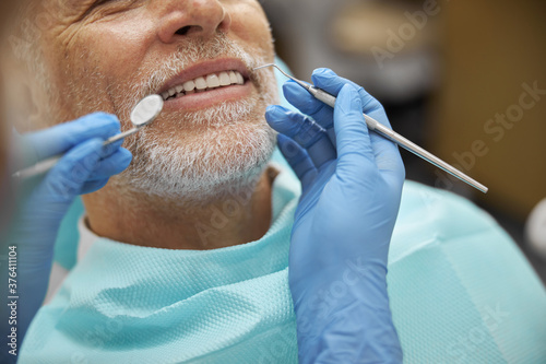 Cuadros en Lienzo Calm elderly man smiling during dental examination