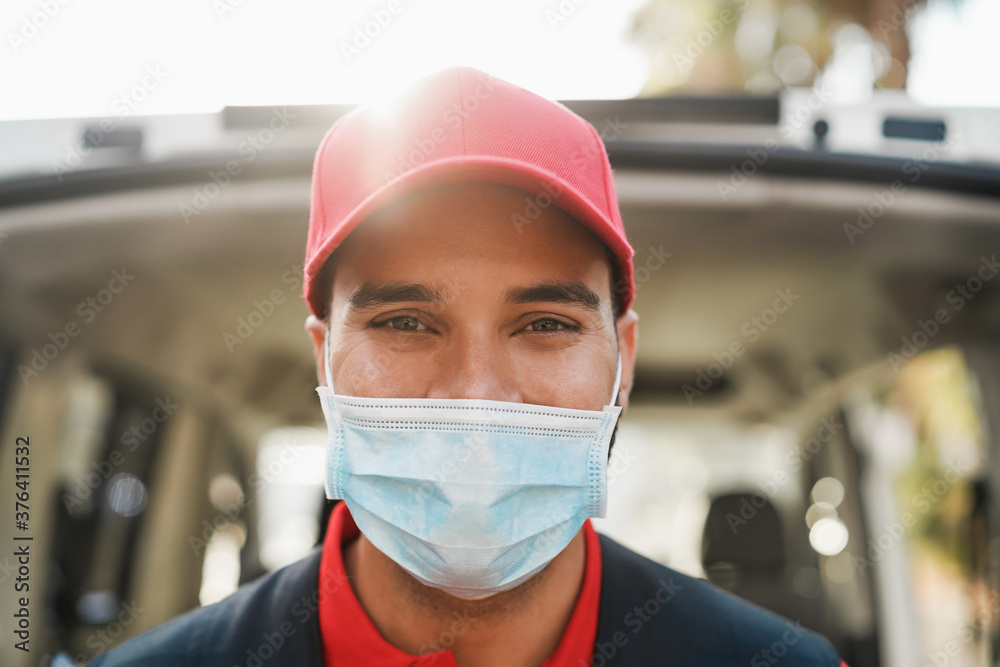 Fototapeta Portrait of delivery man wearing face protective mask for coronavirus spread prevention - Courier person at work during covid 19 pandemic time
