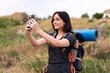 canvas print picture Young mountaineer girl taking a selfie with the mobile with a big backpack at outdoors