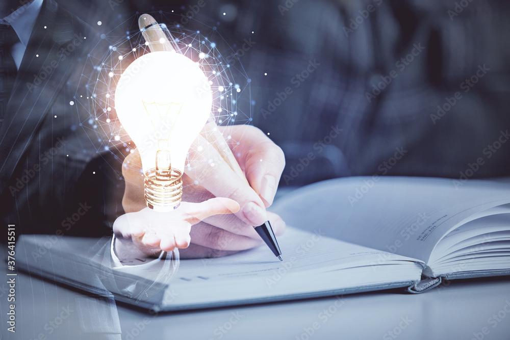 Fototapeta Bulb hologram over hands taking notes background. Concept of idea. Double exposure