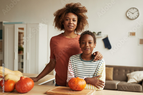 Beautiful African American woman and her teen son standing together at table wit Fototapete