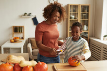 Modern Young Mother And Her Child Standing Together At Table Starting Carving Pumpkins For Halloween