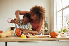 Stylish African American Woman Spending Time With Her Son Standing At Table Carving Pumpkin For Halloween With Kitchen Knife Together