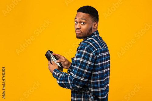Discontented Black Man Holding Wallet With Cash Standing, Yellow Background Canvas Print
