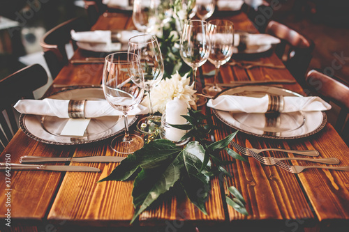 Wedding banquet, serving wooden table with silver plates and decorated with flow Wallpaper Mural