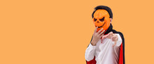 Asian Man Wearing Halloween Costume As Vampire Dracula On Orange Background, Wearing Pumpkin Mask, Looking At Camera
