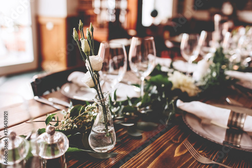 Fototapeta Wedding banquet, serving wooden table with silver plates and decorated with flow