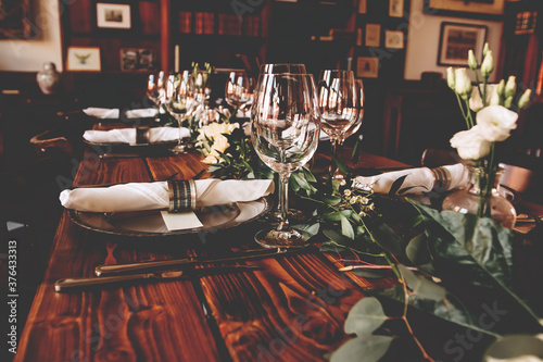 Photo Wedding banquet, serving wooden table with silver plates and decorated with flow