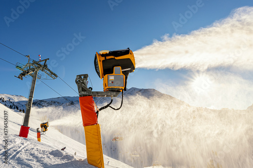 Operating artificial snow cannon near piste making snowy powder Wallpaper Mural