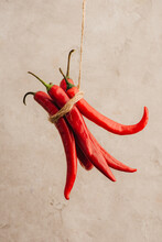 Bunch Of Red Chili Peppers Tied With Rope Hanging On Beige Concrete Background