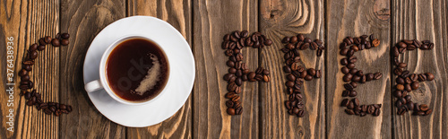 top view of cup of coffee on saucer and coffee lettering made of beans on wooden Fototapeta
