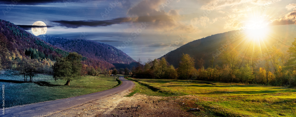 Fototapeta day and night time change concept above country road in valley. wonderful autumn landscape in mountains with sun and moon. forest on hills in colorful foliage. dramatic sky