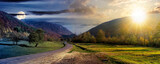 Fototapeta Fototapety na ścianę - day and night time change concept above country road in valley. wonderful autumn landscape in mountains with sun and moon. forest on hills in colorful foliage. dramatic sky