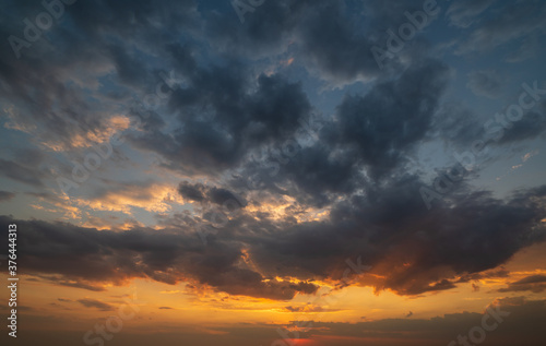 Obraz Summer sunset sky with fleece colorful clouds. Evening dusk good weather natural background. - fototapety do salonu