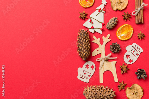 Top view of red background decorated with festive toys and Christmas symbols reindeers and New Year trees. Holiday concept with copy space