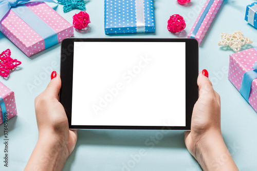 Fotografía Top view of woman holding tablet in her hands on blue background made of Christmas decorations