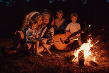 Caring Mother And Father From USA Playing Guitar And Cooking Treat. Family Relaxing Near Bonfire And Camping In The Wood.