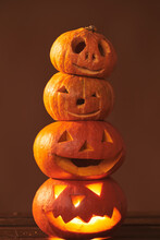 Group Of Four Spooky Handmade Jack O' Lantern Pumpkins Tower Composition, Studio Shot, Brown Background