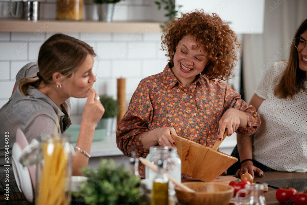 Fototapeta Girlfriends having fun in kitchen. Young women preparing delicious food at home.