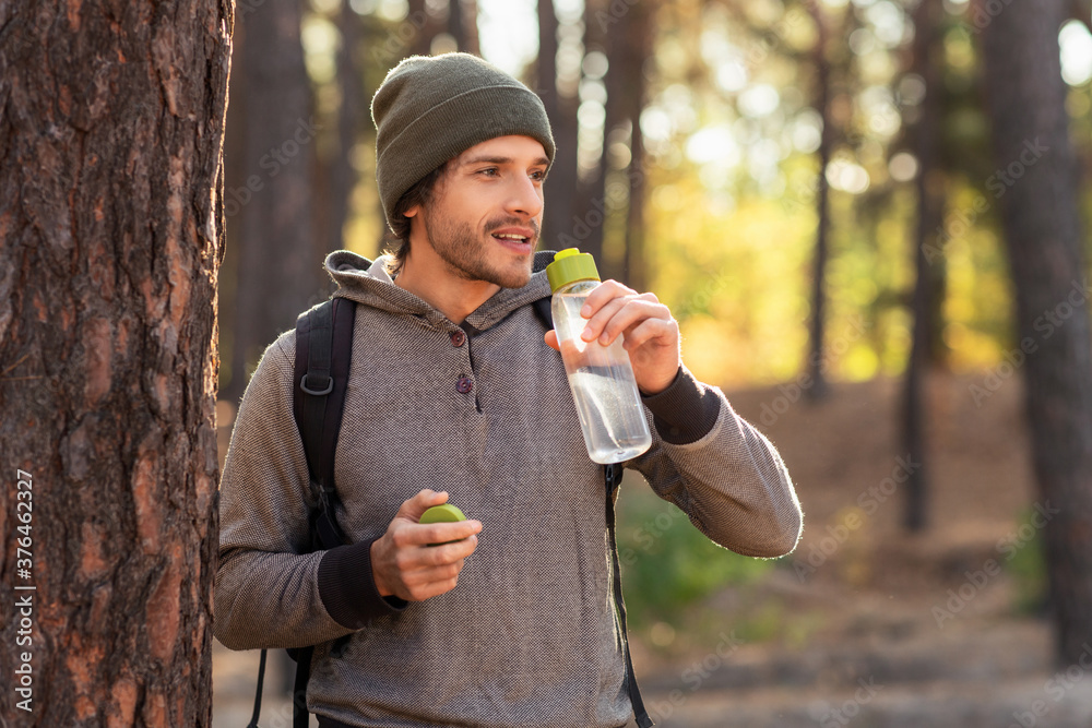 Fototapeta Handsome guy drinking water while walking by forest