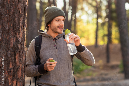 Fotografía Handsome guy drinking water while walking by forest