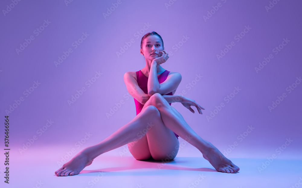Fototapeta Fashion. Young and graceful ballet dancer isolated on purple studio background in neon light. Art, motion, action, flexibility, inspiration concept. Flexible caucasian ballet dancer, weightless jumps.