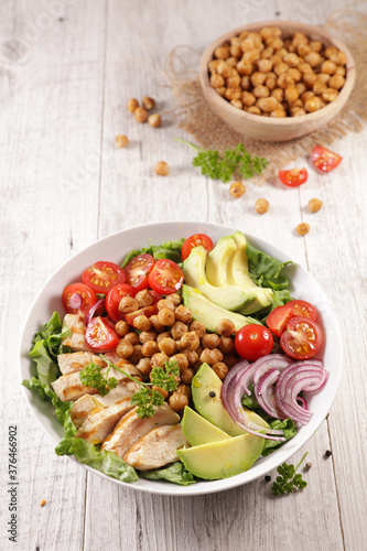 grilled chicken, chickpea, avocado and tomato- vegetable salad with chicken in bowl