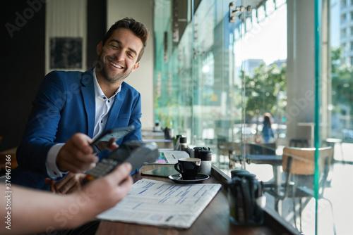 Fotografie, Obraz Smiling man paying his cafe waiter using nfc technology