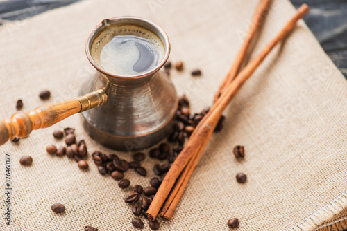 Fototapeta selective focus of cezve with coffee near cinnamon sticks and coffee beans on sackcloth obraz