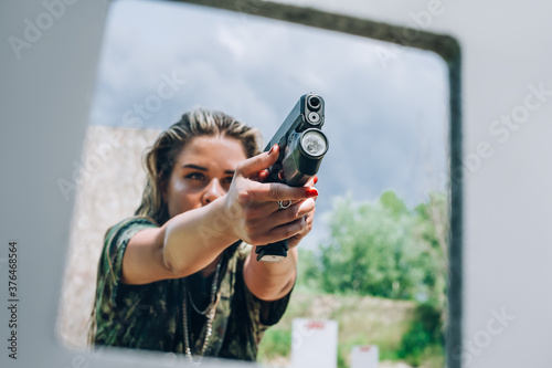 Fotografia Close-up abstract view of attractive female army soldier have gun shooting training from behind and around cover or barricade