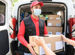 Woman receiving package from delivery man - Young man wearing surgical face mask at work for coronavirus safety measures