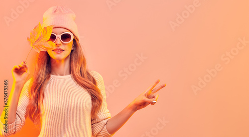 Obraz Fashionable hipster woman in Trendy autumn fall outfit, stylish hair, makeup. Blonde model in jumper, fashion jeans having fun smiling. Beautiful girl in autumnal beanie hat with maple leaf - fototapety do salonu