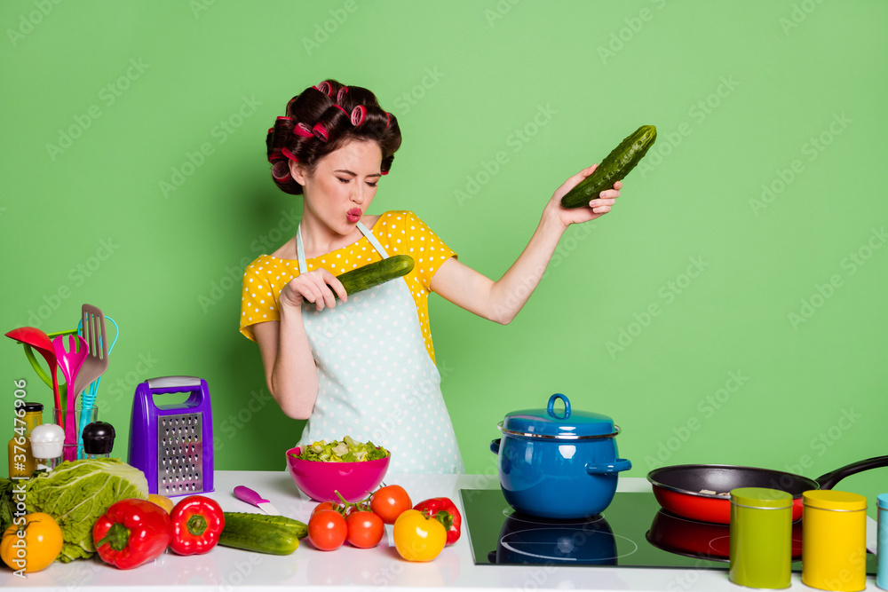 Fototapeta Photo of crazy cool girl prepare supper hold cucumber dance have table pepper tomato ingredients wear hair rollers yellow dotted t-shirt isolated over green color background