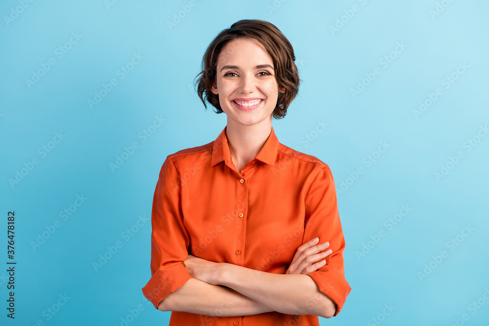 Fototapeta Photo of attractive bossy lady bobbed hairdo arms crossed self-confident person worker friendly smile white teeth good mood wear orange office shirt isolated blue color background