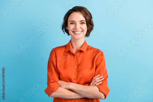 Obraz Photo of attractive bossy lady bobbed hairdo arms crossed self-confident person worker friendly smile white teeth good mood wear orange office shirt isolated blue color background - fototapety do salonu