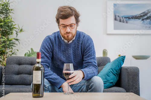 Fototapeta Portrait of man with alcohol drink sitting on sofa at home obraz