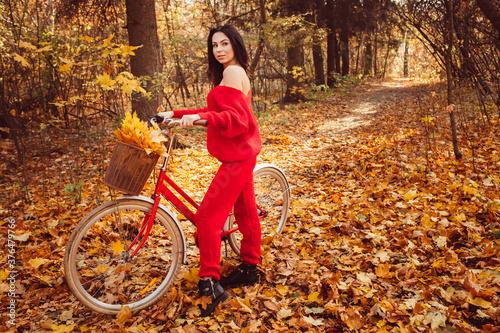 Fototapeta beautiful girl - brunette walks in the autumn forest on a bicycle, golden autumn obraz na płótnie