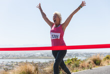Senior Woman Running Towards The Finish Line Ribbon