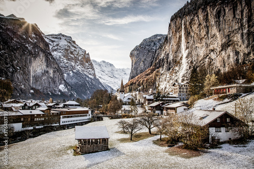 amazing touristic alpine village in winter with famous church and Staubbach wate Fototapet
